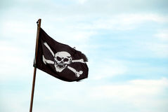 Torn Jolly Roger flies from flagpole Royalty Free Stock Image
