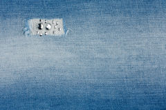 Torn light-blue jeans with rhinestones. Background Royalty Free Stock Photography