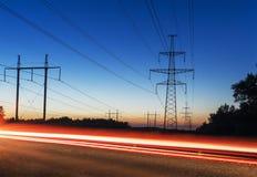 Torn och linjer för maktöverföring på solnedgångspår från bilar Royaltyfri Fotografi