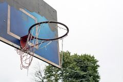 Game over. Torn old basketball hoop, on a grungy pealed off blue board, in a public park against the gray cloudy sky stock images
