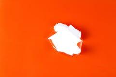 Torn orange paper hole. Tearing Inside white stock image