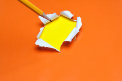 Torn orange paper hole. Tearing Inside yellow Stock Images