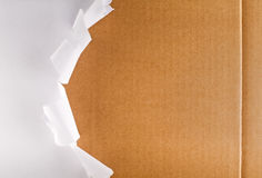 Torn packaging paper revealing cardboard box. Torn wrapping paper revealing brown cardboard box royalty free stock image