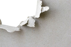 Torn paper. Torn hole in sheet of paper with white background and copyspace royalty free stock images