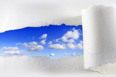 Torn paper on blue sky. With clouds stock photo