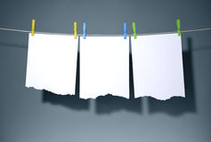 Torn paper on clothespins, dark blue background. Clipping path in file Stock Photo