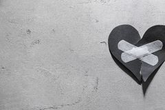 Torn paper heart with medical plasters. On grey background. Relationship problems stock photos