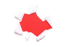 Torn paper hole. Over red background royalty free stock image