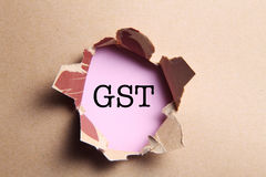 Torn paper. Hole in the paper with torn sides with text GST stock photos