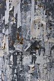 Torn paper on a metal wall. Leftovers of torn paper on a metal wall Royalty Free Stock Photos