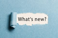 Torn paper revealing the phrase `what`s new?`. Torn paper revealing a phrase `what`s new royalty free stock images