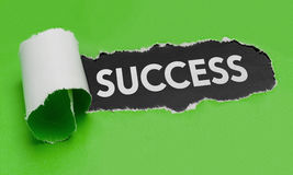 Torn paper revealing the word Success Stock Image