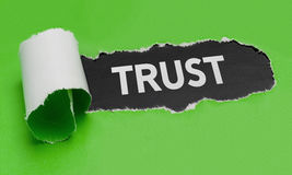 Torn paper revealing the word Trust Royalty Free Stock Photo