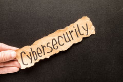 Torn paper with text CYBERSECURITY. In his hand man, against the background of the chalk board stock images