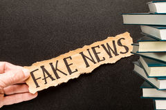 Torn paper with text FAKE NEWS. Torn paper with text FAKE NEWS   in his hand man, against the background of the chalk board Stock Image