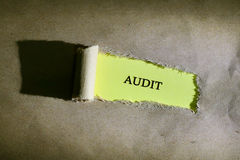 Torn paper with word AUDIT. On yellow background Royalty Free Stock Photo