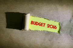 Torn paper with word BUDGET 2016. On yellow background Royalty Free Stock Photos