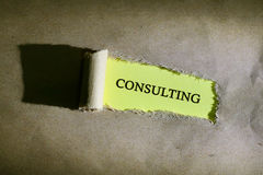 Torn paper with word CONSULTING. On yellow background Royalty Free Stock Photography