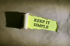 Torn paper with word KEEP IT SIMPLE. On yellow background Royalty Free Stock Photography