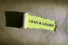Torn paper with word LEAD & LEARN. Torn paper with word LEAD & LEARN on yellow background Stock Photo