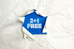 Two plus one free. Torn paper writing Two plus one free royalty free stock photos