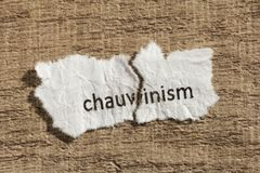 Torn paper written chauvism over wood table. Concept of old and Royalty Free Stock Photos