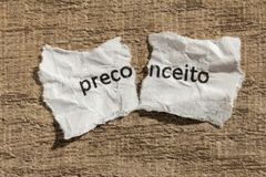 Torn paper written preconceito, portuguese word for prejudice, o. Ver wooden background. Old and abandoned idea or practice. Macro photography Stock Photography