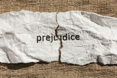 Torn paper written prejudice over wood table. Concept of old and. Torn paper written prejudice over wooden background. Old and abandoned idea or practice. Macro Stock Image