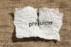 Torn paper written prejuicio, spanish word for prejudice, over w. Ooden background. Old and abandoned idea or practice. Macro photography Stock Images