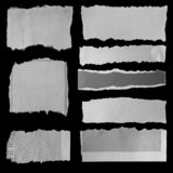 Torn papers on black. Eight pieces of torn newspaper on black background royalty free stock photography