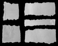 Torn papers on black. Five pieces of torn newspaper on black background stock photos