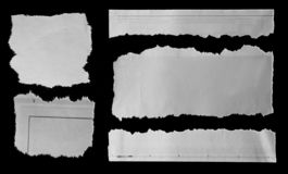 Torn papers on black. Five pieces of torn newspaper on black background stock photography
