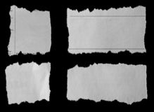 Torn papers on black. Four pieces of torn newspaper on black background royalty free stock photos