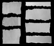 Torn papers on black. Seven pieces of torn newspaper on black background royalty free stock photo