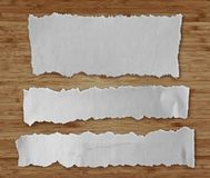 Torn papers on wood. Three pieces of torn newspaper on wooden background stock photography