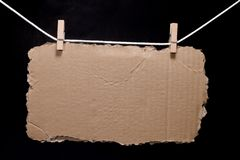 Torn piece of cardboard hanging on rope attached with clothes pins. Torn piece of cardboard. Corrugated cardboard torn edge for use as a background stock photo