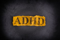 Torn piece of paper with abbreviation ADHD. Concept Image. ADHD is Attention deficit hyperactivity disorder. Close up. Vignette stock photos