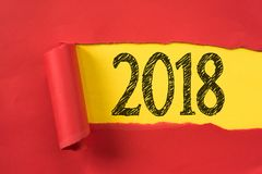 Torn piece of red paper uncovering 2018 underneath. New year concept Stock Image
