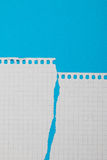Torn pieces of checkered paper. On blue background Royalty Free Stock Image