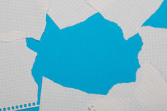 Torn pieces of checkered paper. On blue background Stock Photo