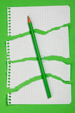Torn pieces of checkered paper. On green background Stock Photo
