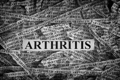 Torn pieces of paper with word Arthritis Stock Image