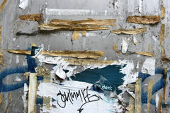 Torn poster. S on old wall, signs of graffiti, vandalism and urban decay royalty free stock image