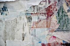 Torn posters. Colorful torn posters on grunge old walls as creative and abstract background stock photo