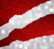 Torn red paper with glitter lights over silver bokeh lights background Stock Photos