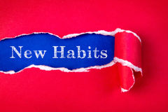 Torn red Paper and New Habits text. With  a blue paper background Stock Image
