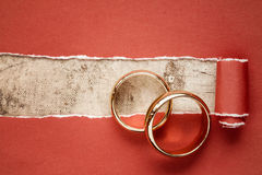 Torn red paper and wedding rings Stock Image