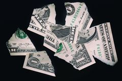 Torn ripped devalued one dollar bank note on a black background. stock image