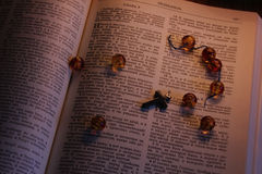 Torn rosary on an open Bible Stock Image