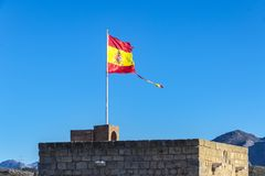 Torn Spanish flag waving on the wind Stock Photos